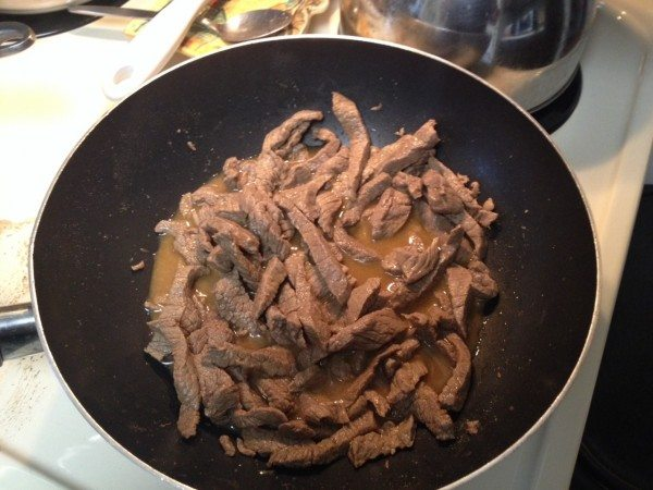 Beef strips in wok with soy sauce and orange juice