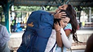 Two women hug at a train station. One wears a large blue backpack.