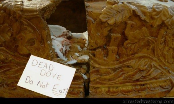 "A picture of the wedding pie from Game of Thrones with a sign that says ""Dead dove, do not eat."""
