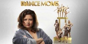 Photo of Abby Lee Miller standing in front of her dancers against a grey background.
