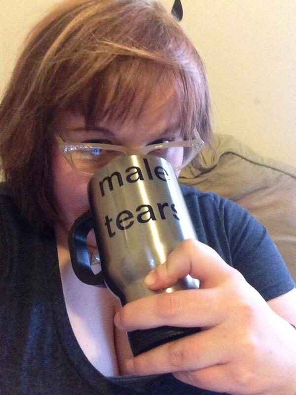 """A picture of a woman drinking from a silver mug that says """"male tears"""" on it."""
