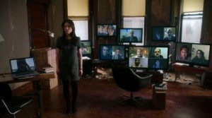 Joan standing in front of monitors with the faces of hackers staring back.