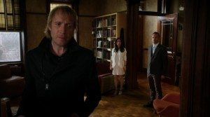 Mycroft standing on forefront with Joan and sherlock looking at him from behind.