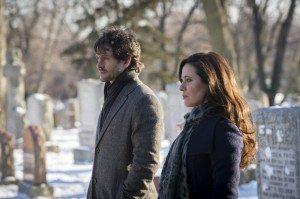 A man and a woman stand in a grave yard