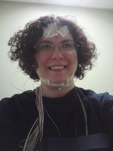 A woman with wires taped to her forehead and chin, and more wires around her neck.