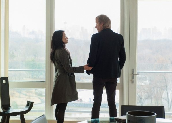 Joan and Mycroft standing in front of a huge window with Joan touching Mycroft's arm.