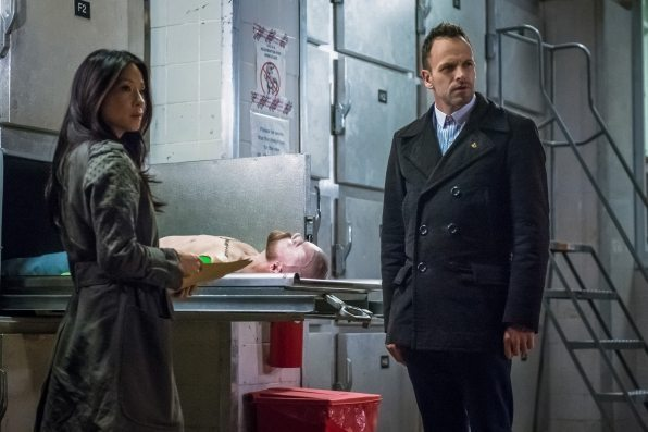 Joan and Sherlock standing over an armless body in the morgue.