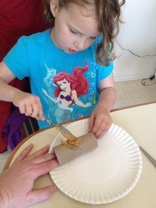 Little girl spreading peanut butter onto a toilet paper roll.
