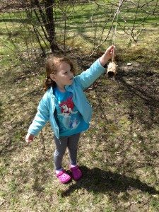 Little girl reaching up to hang the finished bird feeder over a branch.