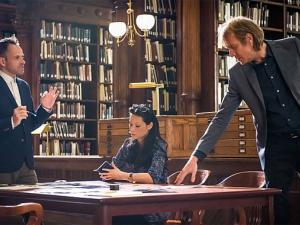 Sherlock, Joan and Mycroft around a table in a library. Sherlock and Mycroft are standing and Joan is sitting.