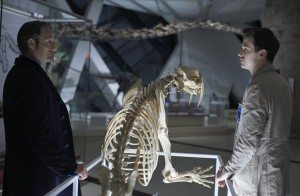 Two men stand separated by a skeleton of a saber toothed tiger