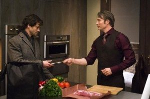 Two men are in a kitchen preparing food
