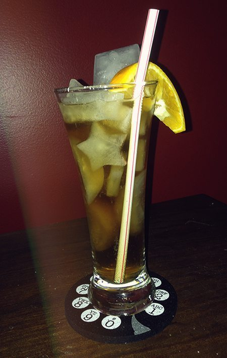 Long Island iced tea in a clear glass with an orange garnish, and a Han Solo in carbonite ice cube.