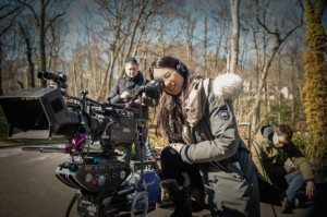 Lucy Liu looking into a film camera as she directs