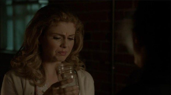 Cathy grimaces as she drinks from a Mason jar.