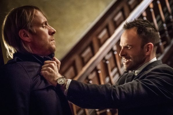 Sherlock has Mycroft by the throat and Sherlock looks very angry