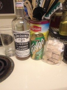 A tall glass, a Bottle of Jacquin's Ginger Brandy, a can of Faygo ginger ale, and a bag of crystallized ginger.
