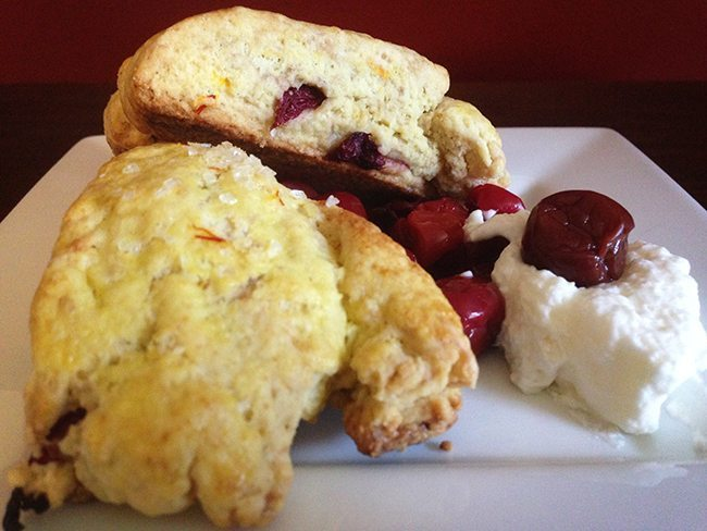 Two saffron cherry scones on a plate with whipped cream and dried cherries.