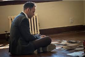 Sherlock sitting on a floor in a bare room with evidence in front of him.