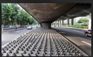 Below an over pass, a series of pyramidal spikes designed to deter homeless people from camping out of the rain