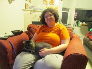 A grey cat sits on a woman's lap.
