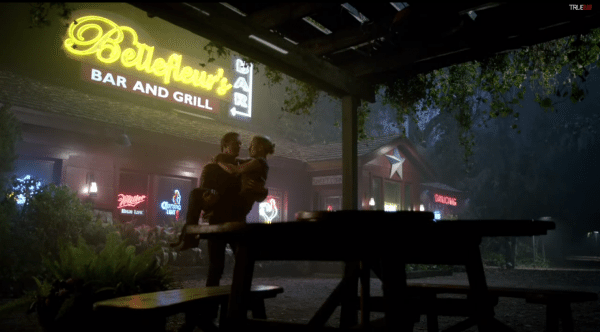 Eric cradles Sookie in front of the bar.