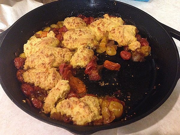 Tomato casserole, topped with biscuits, in a cast iron pan.