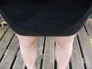 Bare knees and legs under a black skirt