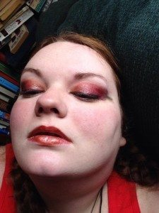 A pale heavy redhead wearing eye shadow that looks like chilis and a coppery lip makeup.