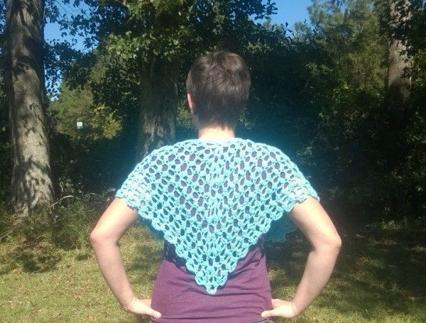 The back of a blue crochet wrap.