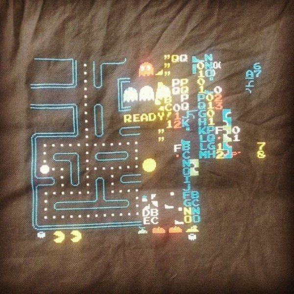 A picture of the Pac-Man kill screen being cross stitched only black fabric.