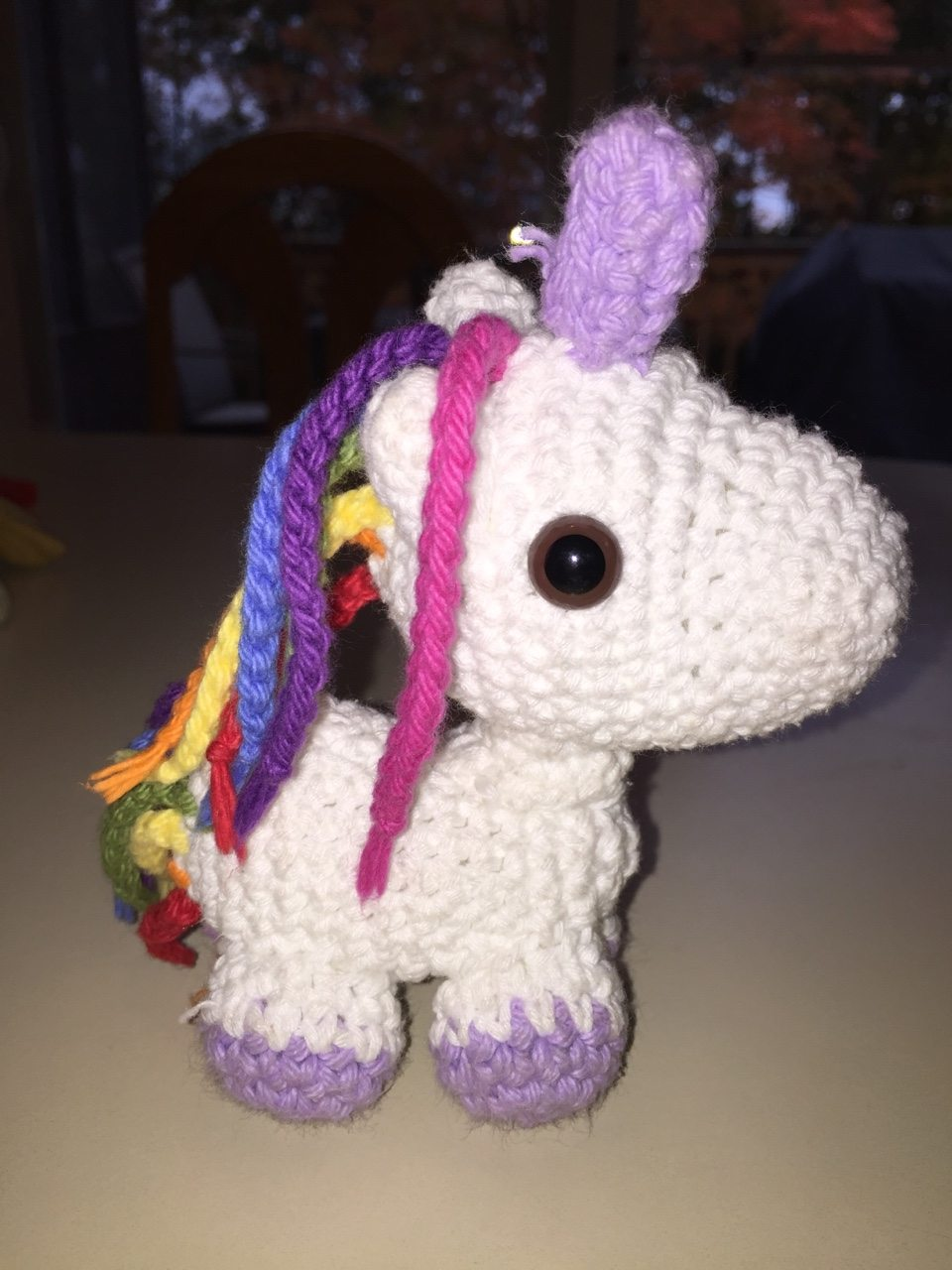 white amigurumi unicorn with rainbow hair and a lavender horn