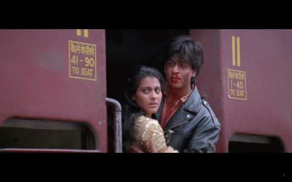 A woman wearing gold and a man with a bloody nose embrace on a train.