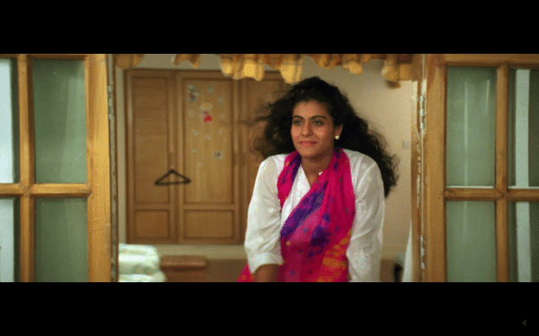 A screenshot of a brown-skinned woman with long black hair wearing a white top and bright pink scarf.