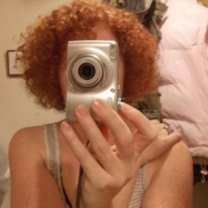 A picture of a woman with red curly hair, her face obscured by a camera.