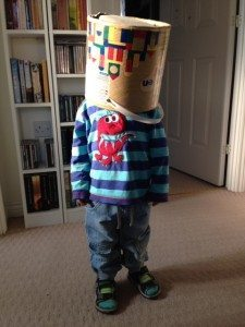 Small boy with toy bucket over his head