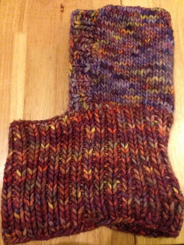 A picture of a thick knitted cowl with a hood laying flat on a wood surface.