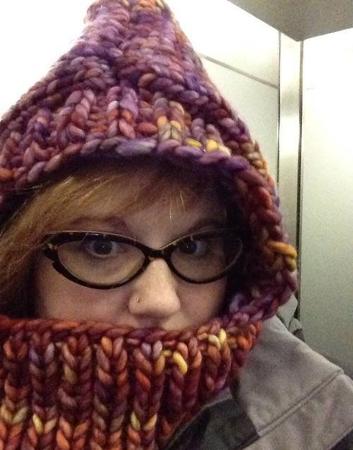 A picture of a readheaded woman in cat-eye glasses wearing a very thick knit cowl with a hood.