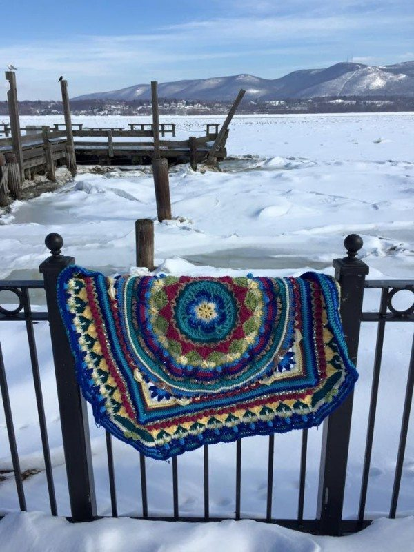 A crocheted blanket hanging on a railing in front of a frozen river.