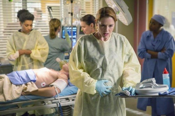 Screencap from Grey's Anatomy of Dr. April Kepner turned away from a patient, with one hand on her pregnant belly.