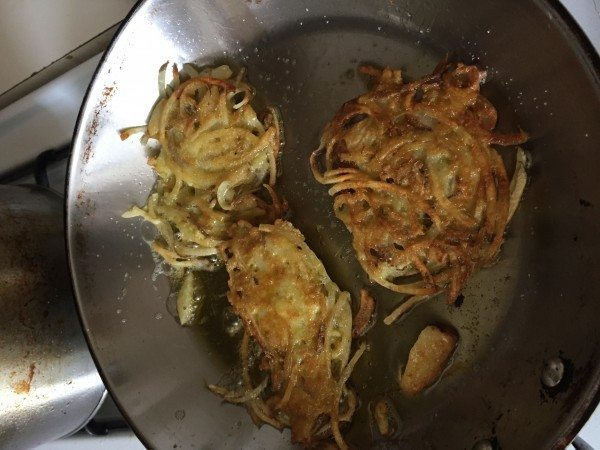 A picture of three potato latkes in a frying pan.